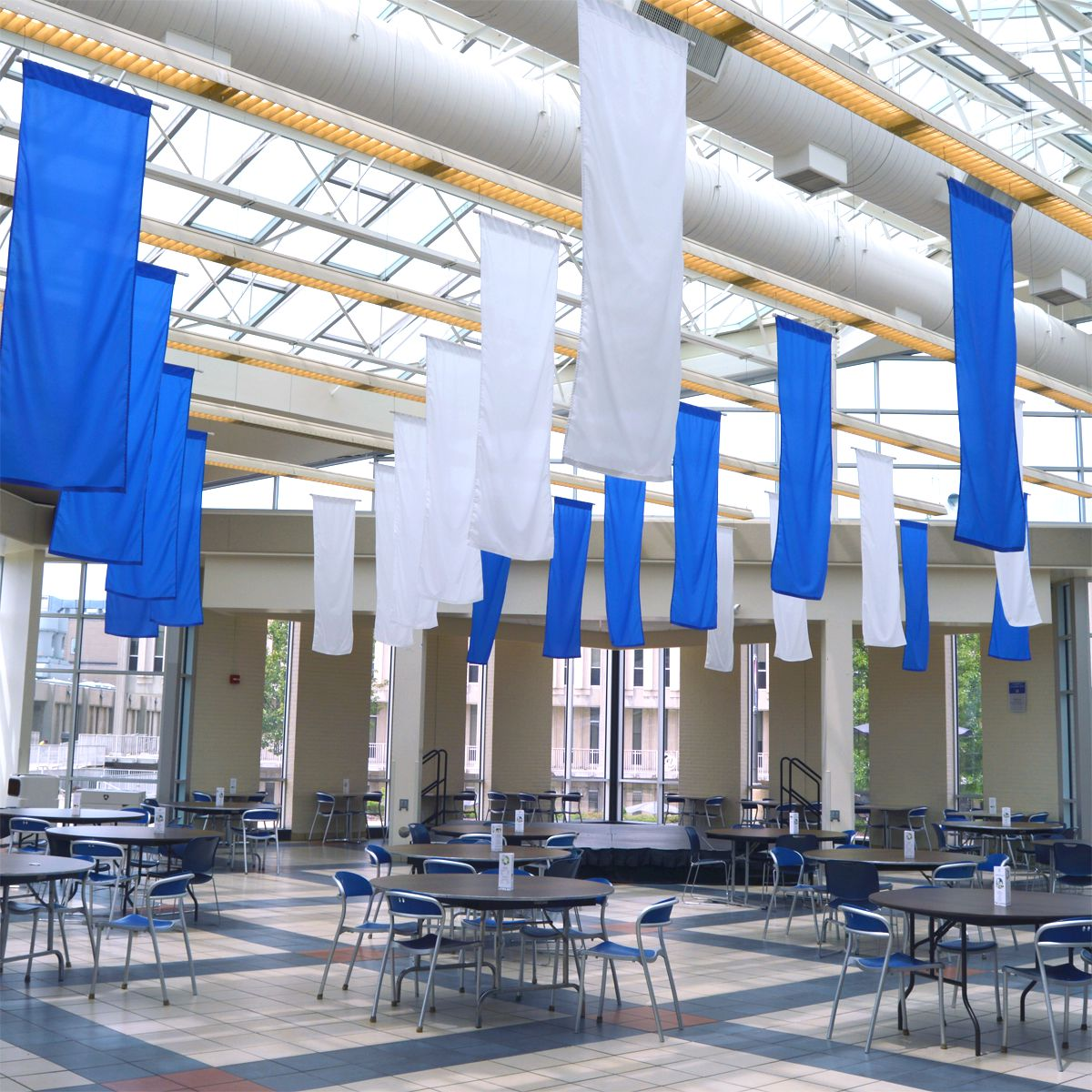 Student Center with empty tables and blue and white flags
