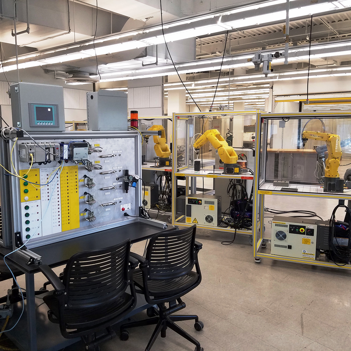 Photograph of the inside of a lab with fanuc robots and other machinery