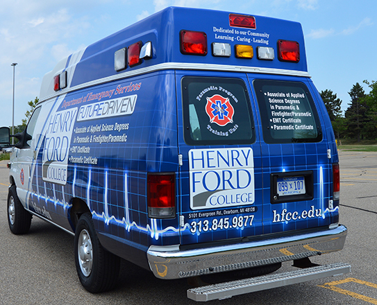 The rear and sides of the ambulance list the EMS programs available at HFC.