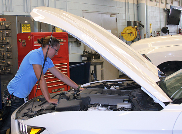 Ashley Smith, HFC's first automotive faculty member, checks under the hood of a car.