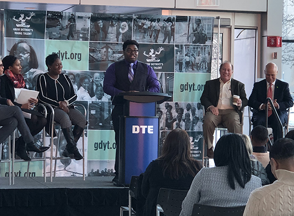 Tyrone Bean presents at the DTE headquarters, flanked by Mayor Mike Duggan (second from right) and other leaders.