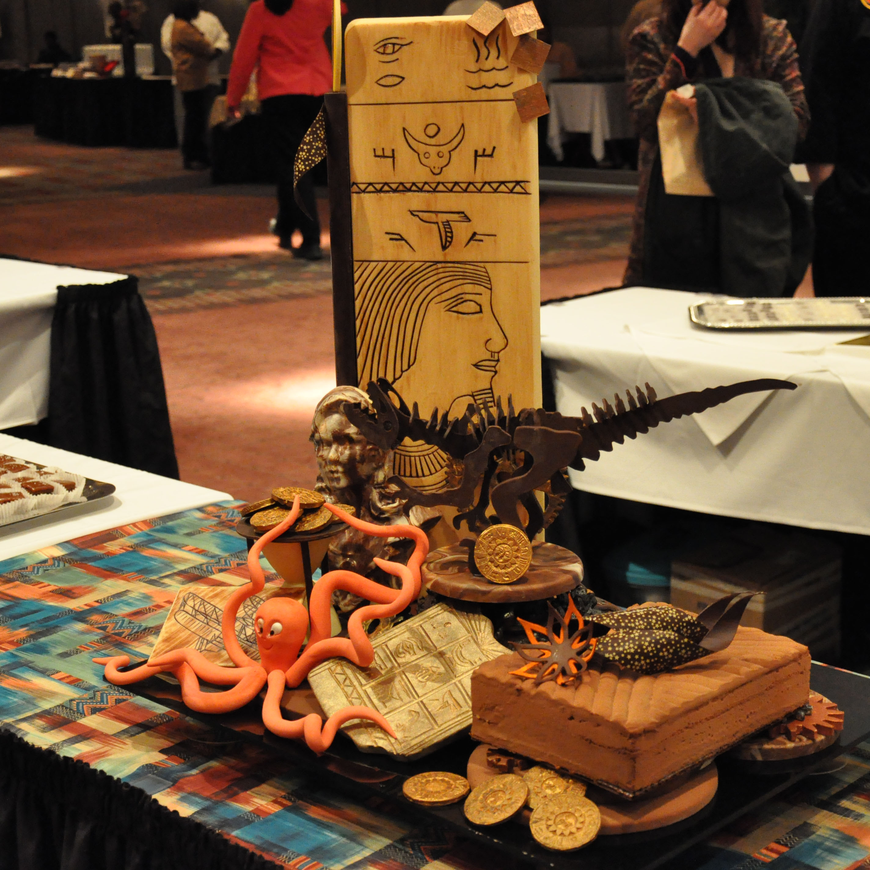 Ornate edible chocolate sculpture of ancient relics, gold coins set on display at a dessert competition