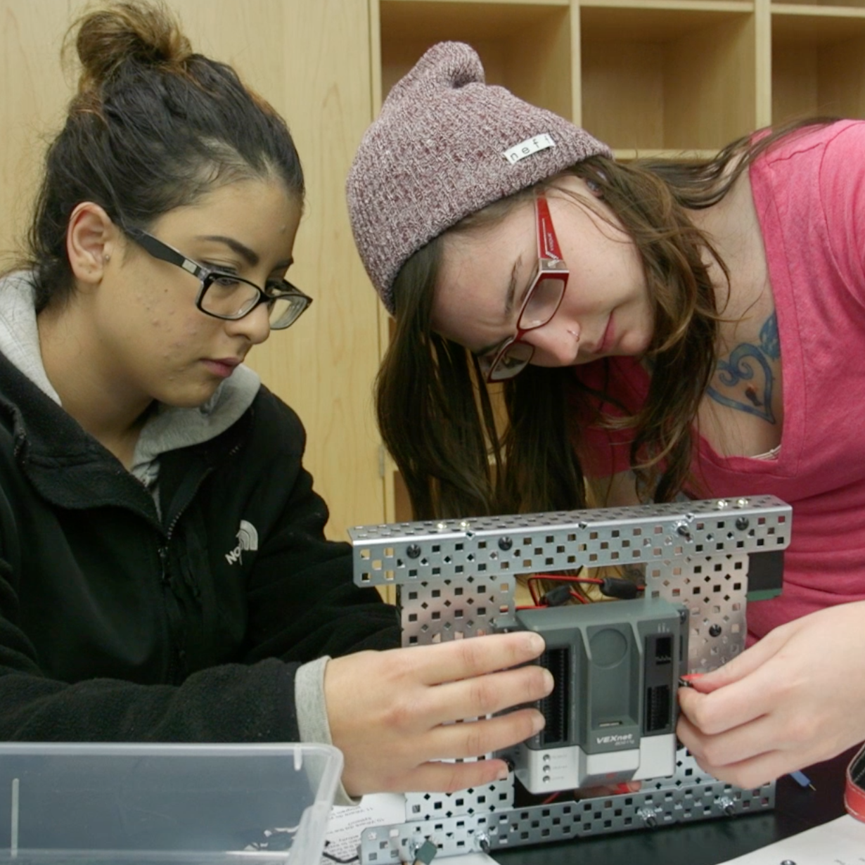 Two students concentrating and examining a small robotic machine's underside