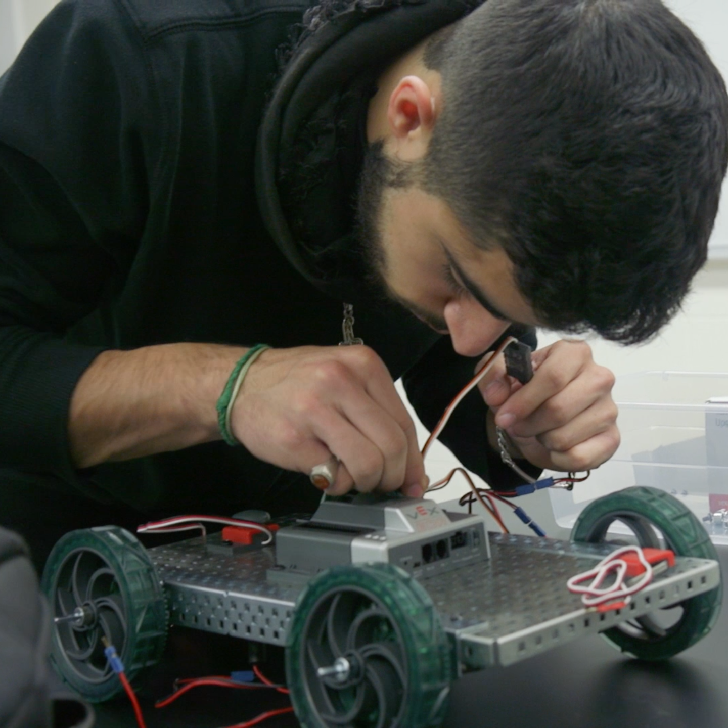 Student leaning over a robotic vehicle, arranging wires