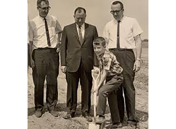 The 1966 groundbreaking ceremony of MCCC. From L to R: MCCC board member Fred Gruber, State Rep. Ray Kehres, Kevin Campbell (digging), and Dr. Ronald Campbell, MCCC's founding president. Campbell's son was 8 at the time of the groundbreaking and helped his father dig the first ceremonial shovels of dirt.