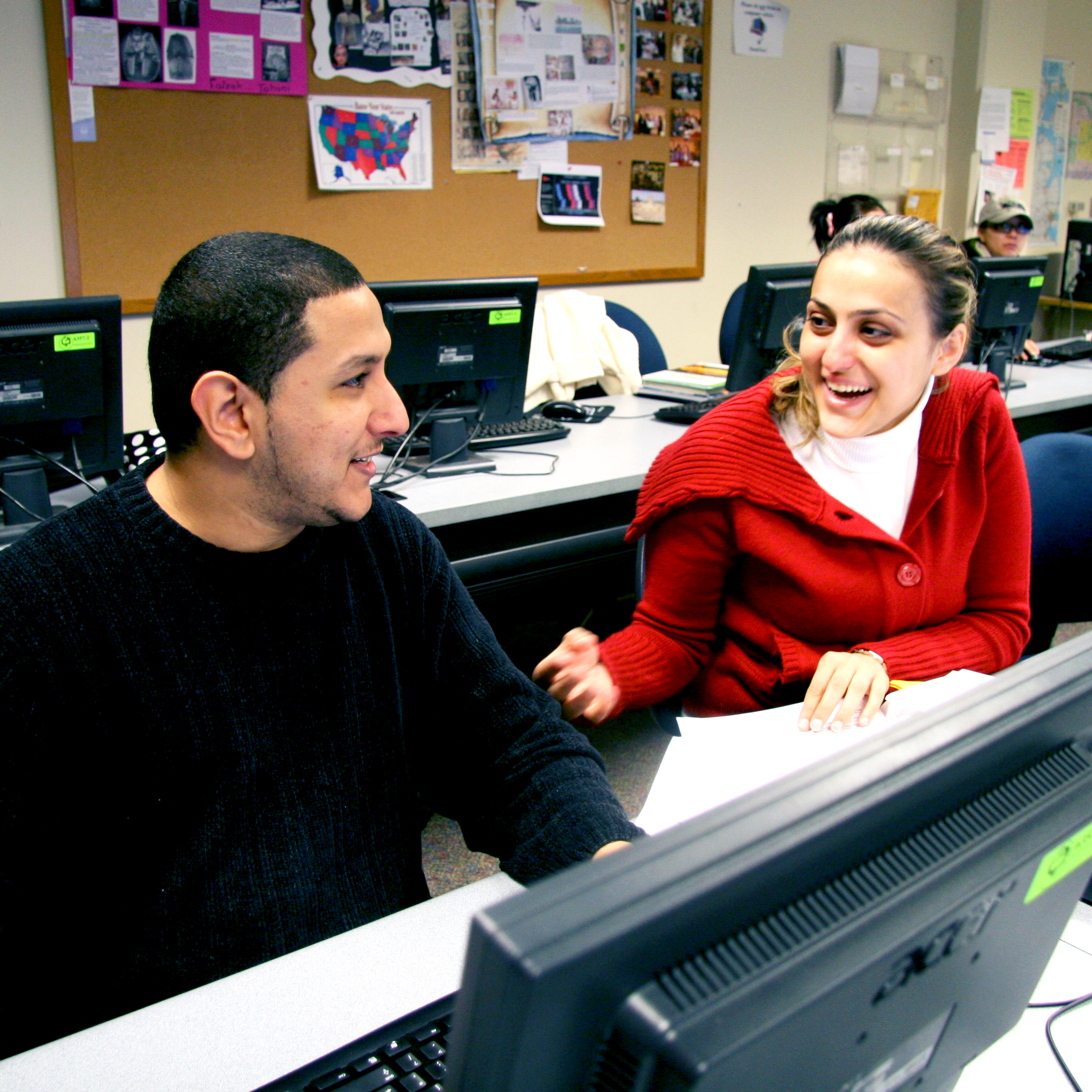 Two students laughing and talking in a classroom computer lab