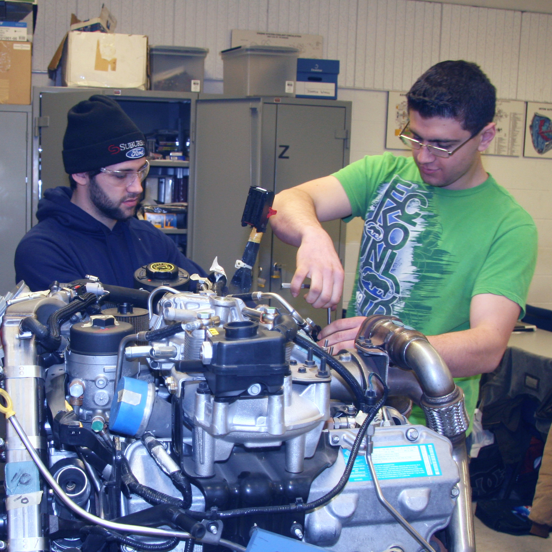 Two students working on large automotive engine