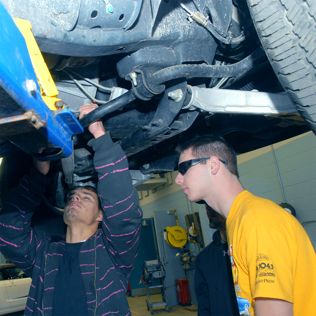 Two students standing underneath car lifted by a jack, the one on the left peering at the underside's parts and reaching up to work on it