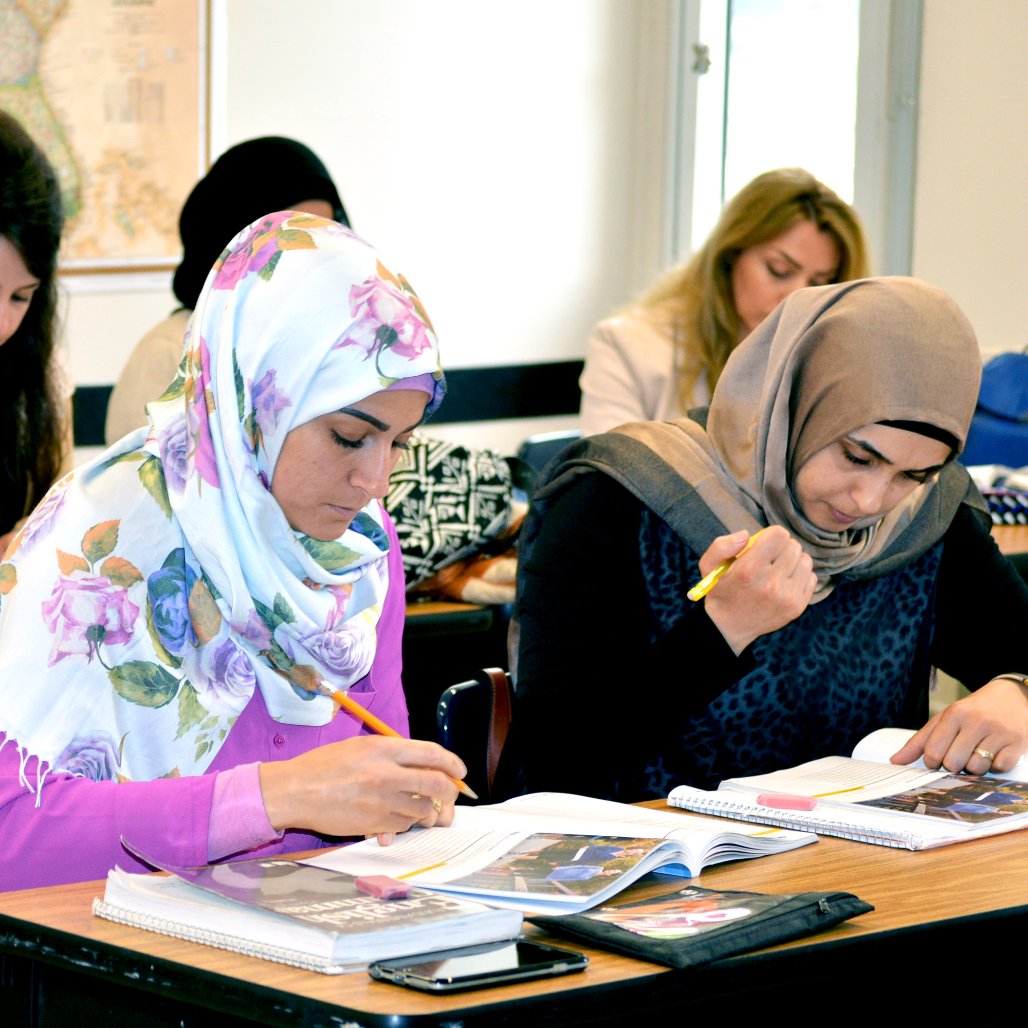 Group of students highlighting passages in textbooks in a classroom