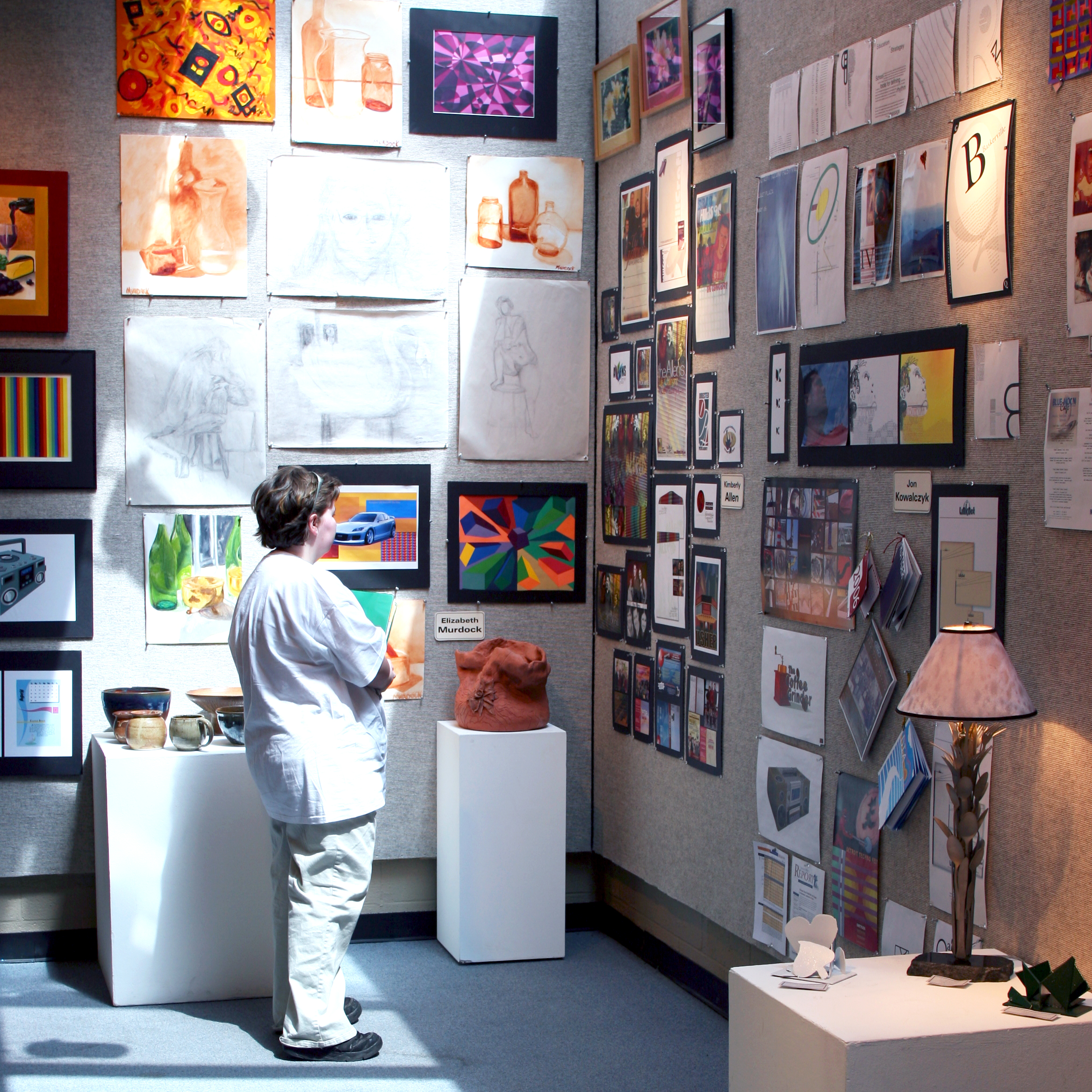Student views two walls covered in a vast array pf framed artwork created by HFC students.
