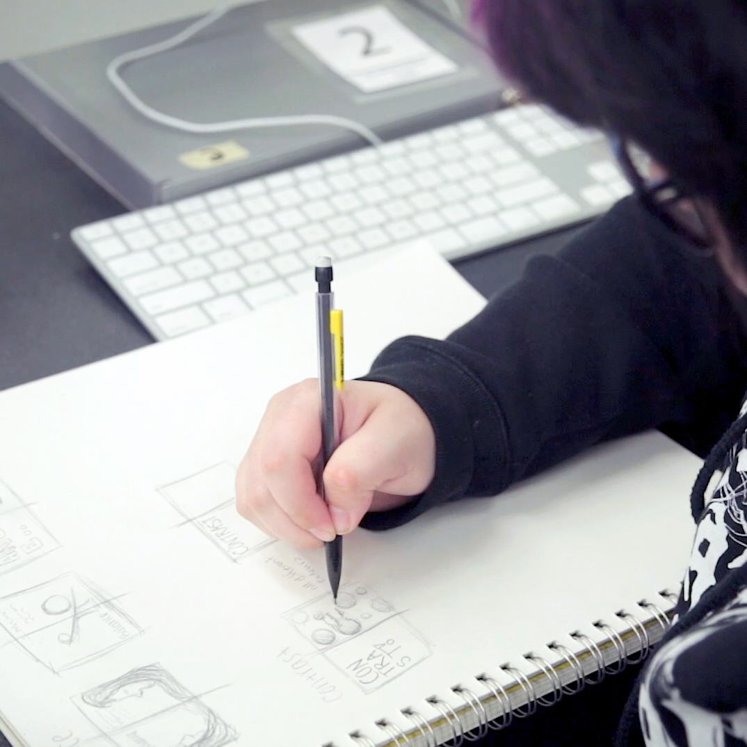 Closeup of student creating multiple thumbnail sketches in graphite in a sketchpad