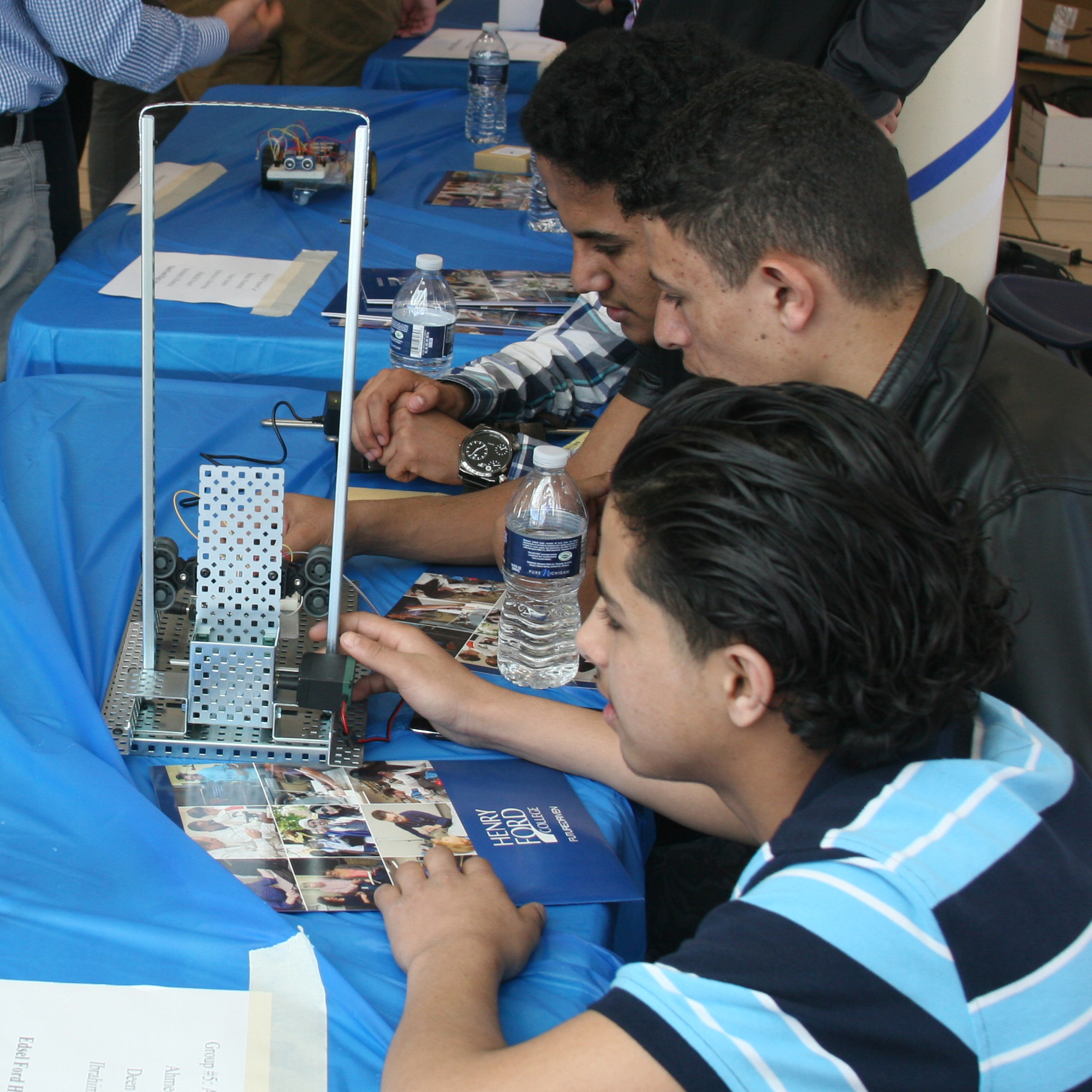 Group of four people sitting at a booth showcasing a robotic vehicle