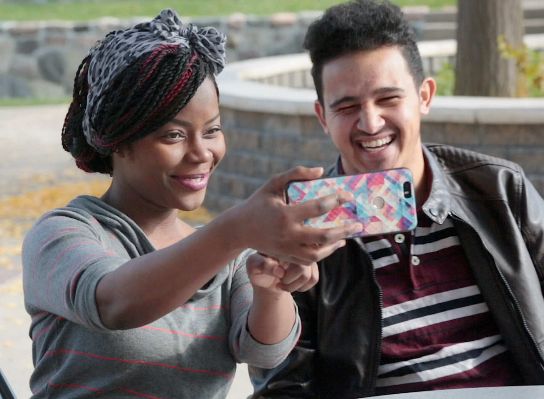 Two smiling students taking a photo of themselves with a cell phone