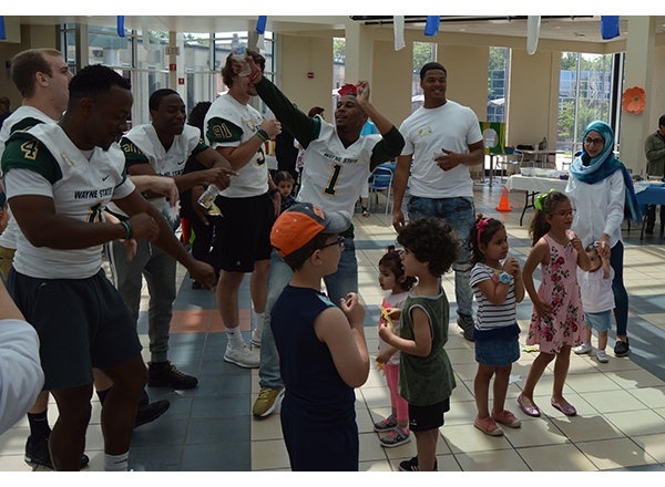 Members of the Wayne State University football team dance along with kids at the 4th Annual Family Literacy Event.