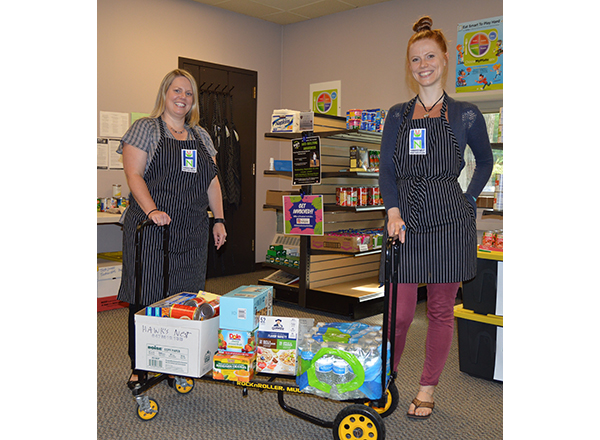 HFC Student Activities Associate Mandy Earl and HFC student Lucy Smith catalog the food items donated to the Hawks' Nest.