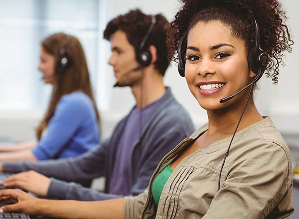 A smiling customer service representative with other customer service professionals in the background.