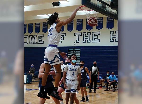 An image of an HFC basketball player dunking a basketball.