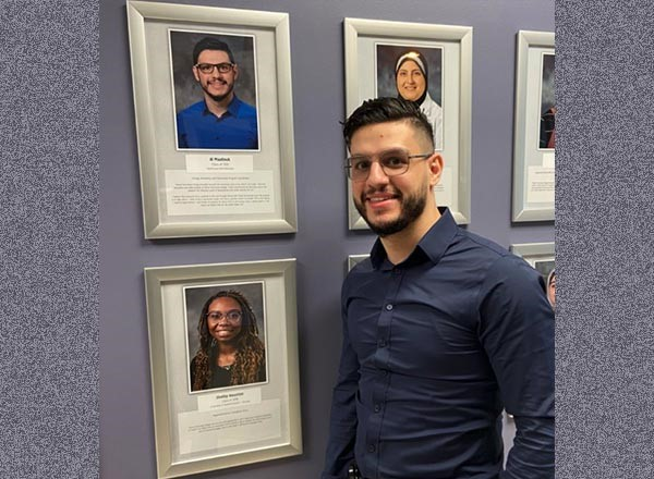 Photograph of HFEC alumnus standing before the Wall of Fame at HFEC.