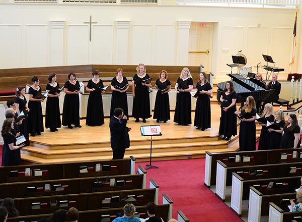 women in a row, singing