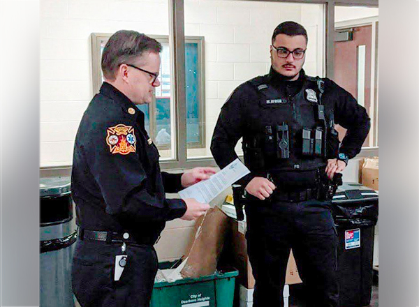 Dearborn Heights Fire Department Chief David Brogan (left) reads a letter of commendation to Dearborn Heights police officer and HFC alumnus Mehdi Ayoub (right), who resuscitated a toddler last fall, saving the child's life. Photo courtesy: City of Dearborn Heights.