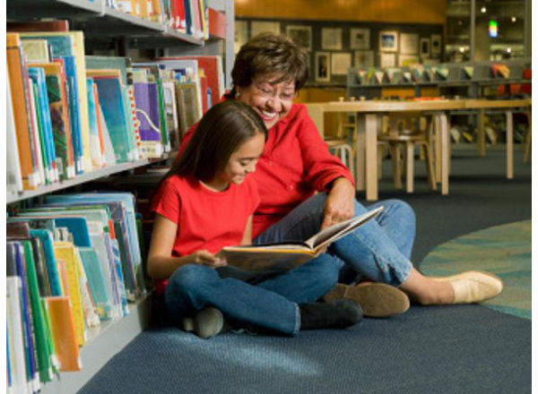 Photo of grandmother reading with her granddaughter in a library. From the Colorin Colorado website.
