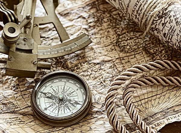 Image of sailing tools of the 15th century: sextant, compass, map, rope.