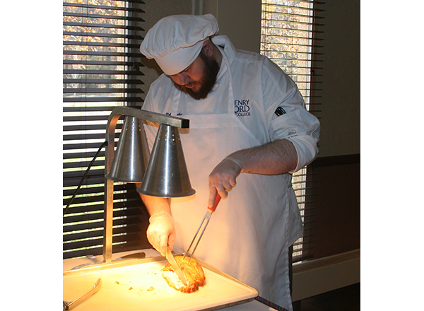 HFC student Robert Thacker carves meat during a buffet