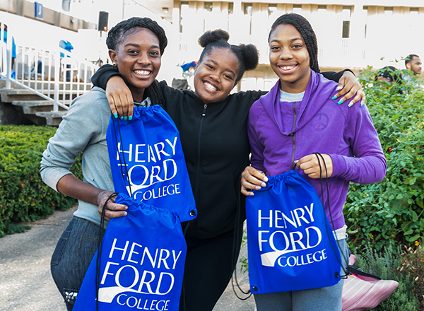 Three students holding HFC backpacks