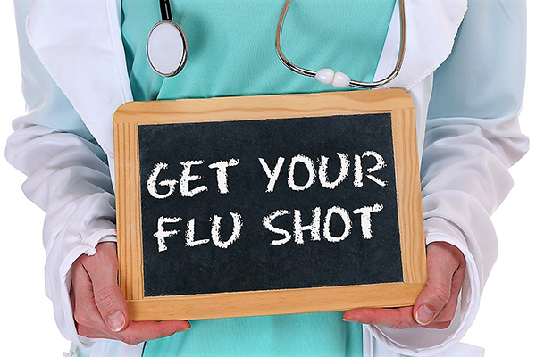 "health care worker holding a sign with ""Get Your Flu Shot"""