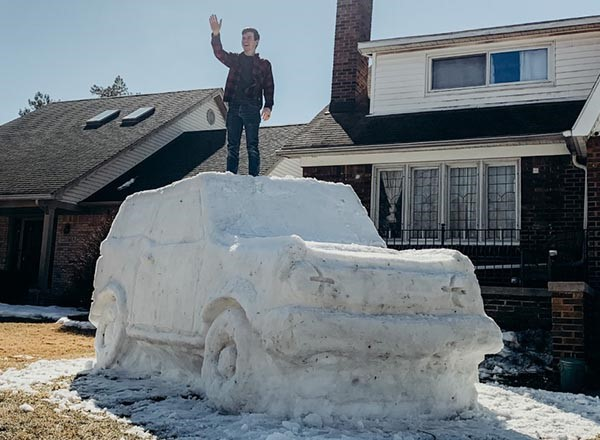Man standing, waving, on top of snow sculpture