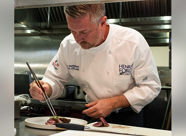 Chef Eric Gackenbach puts the finishing touches on an entree in HFC's student-run restaurant, Fifty-One O One.