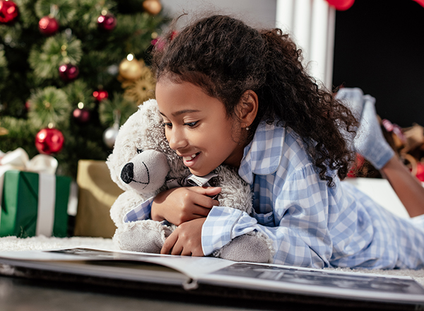 Child reading a book holding a teddy bear