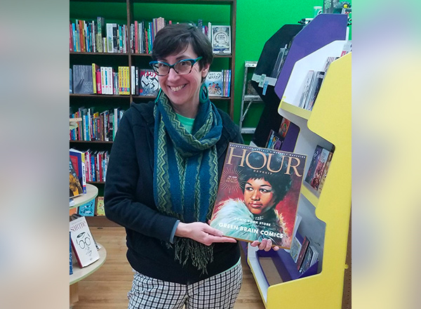 "HFC alumna/Green Brain Comics co-owner Katie Merritt shows off her award given to her Dearborn-based comics store by Hour Detroit Magazine. Readers voted Green Brain ""Hour Detroit's Best of Detroit Comic Book Store – Single Location.""  To make this award a bigger thrill, her store is named on the cover that features the late Aretha Franklin."