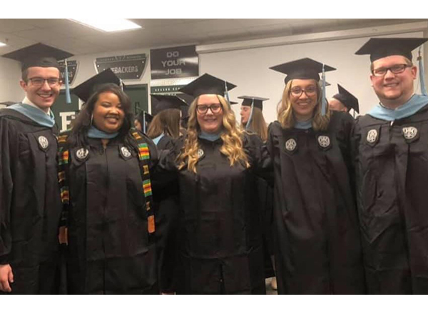 Photo of 5 employees (2 men, 3 women) in graduation attire