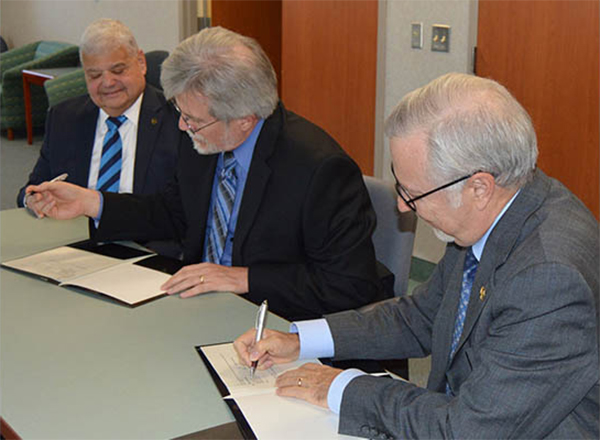 From left to right: Dr. Michael Mazzeo, dean of the Oakland University School of Business Administration; Dr. Daniel Herbst, HFC Vice President of Student Affairs; and Dr. James Lentini, Oakland University Provost and Sr. Vice President for Academic Affairs, sign the articulation (transfer) agreement between the two educational institutions earlier this month at HFC.