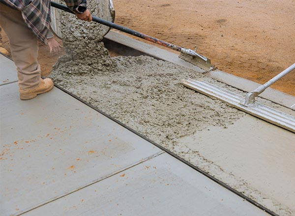 Sidewalk being repaired by a construction worker.