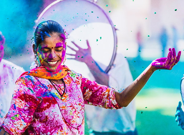 Hindu woman dancing with many colors on her face, clothing, and hair.