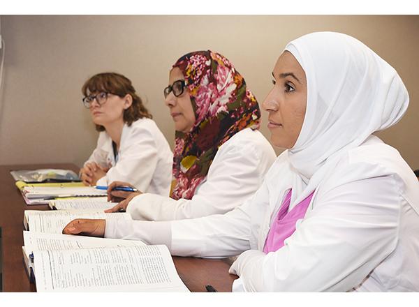 Photo of Lauren Fisher, Nudrat Jehan, and Halah Hassan in class