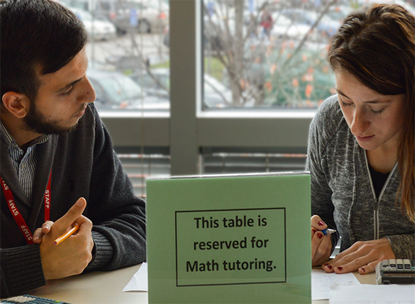 Tutor and student at a table with a sign that the table is reserved for tutoring