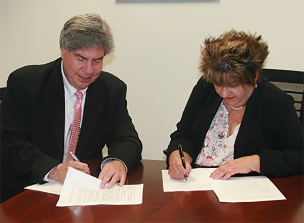 Dr. Michael Nealon (left), HFC Vice President of Academic Affairs, and HFC AFO President Lynn Boza (right) sign the memorandum of agreement.