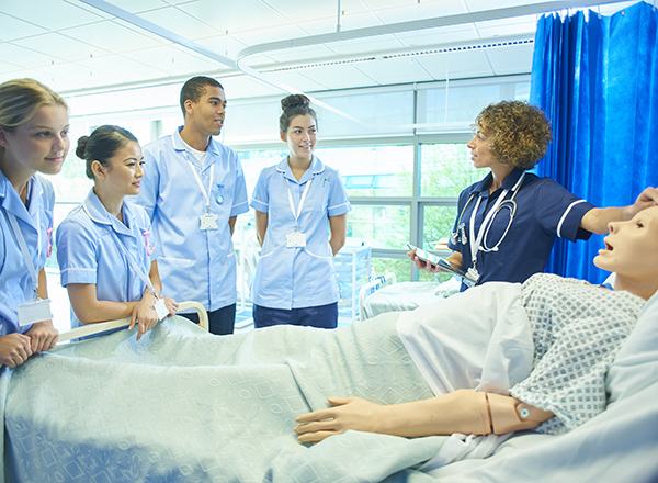 Nursing students around a simulation mannequin