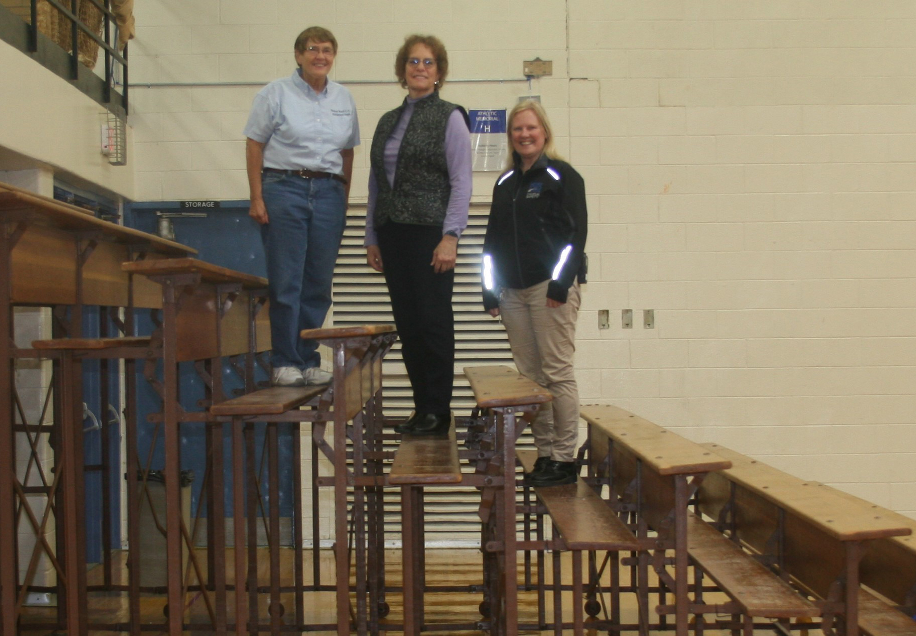 Bryden, Perkovich, and Schoen standing on the old bleachers