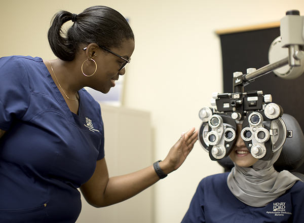 Ophthalmic technician in the HFC lab learning to conduct an eye exam