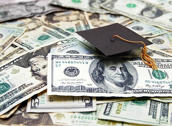pile of money with a graduation cap
