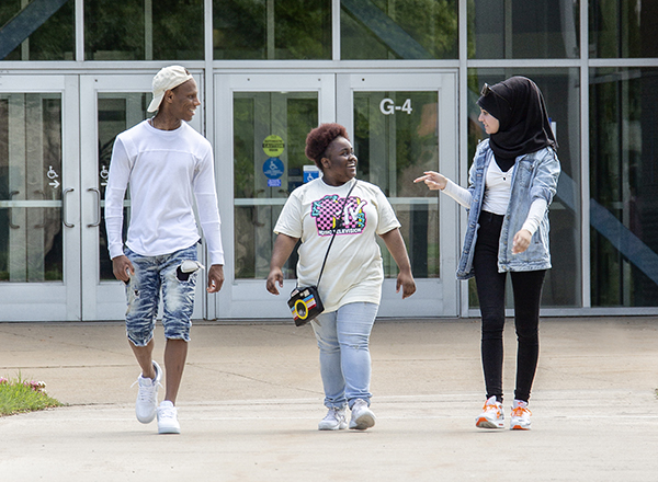 Image of three students walking in front of the Health Careers building