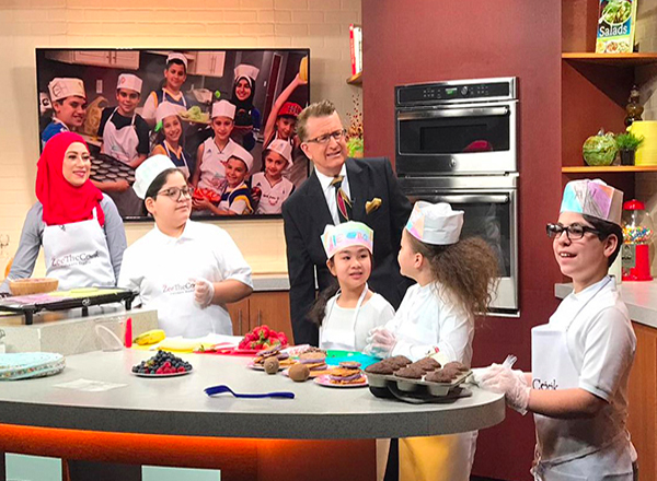 Zee Shami (left) and her culinary students cook breakfast for FOX 2's Charlie Langton (center) in February 2020.