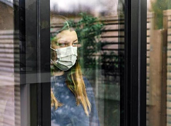 Image for social isolation workshop (woman in a mask staring out a window)