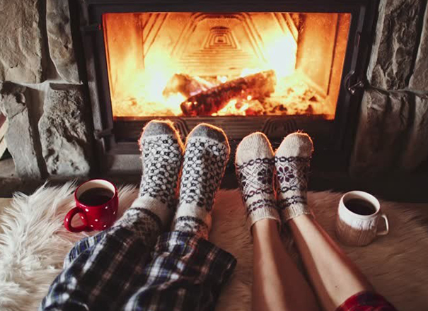 Photo of 2 pairs of feet warming up at a fire.