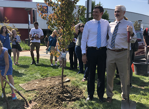 Two men standing next to a tree
