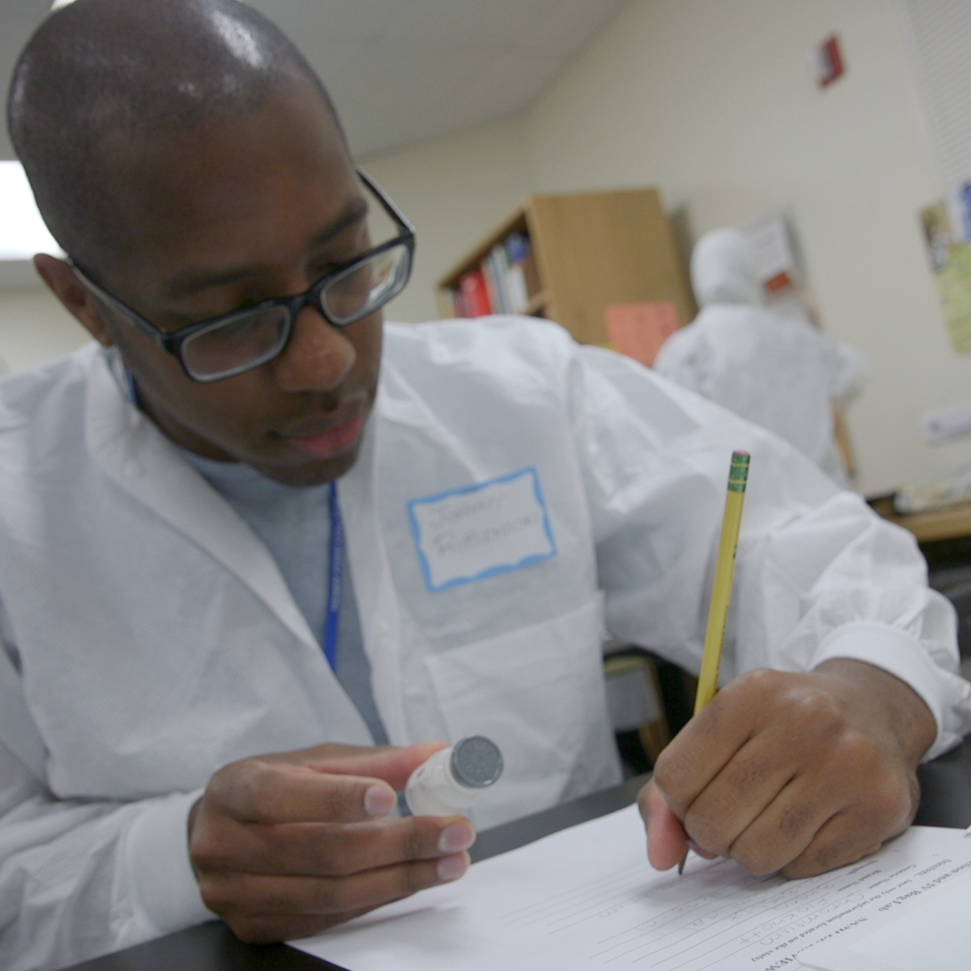 Student in white lab coat writes medication information while holding a vial.